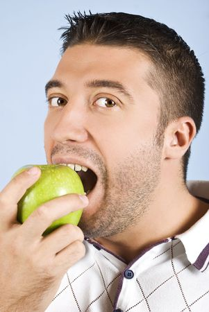 Male portrait taking  a bite of an apple and looking you on blue background photo