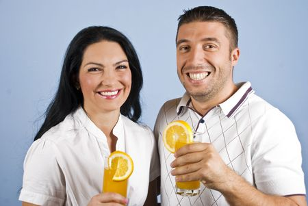 Extremely happy healthy couple laughing and holding glasses with fresh oranges juice on blue background photo