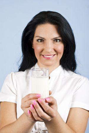 Happy woman holding  a glass with milk with both hands in front of image,focus on glass milk photo