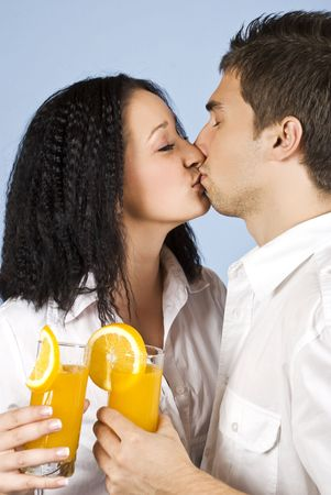 Two young people couple kissing and holding glasses with fresh orange juice photo