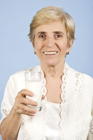 Healthy old woman holding a glass milk and smiling for you on blue background photo