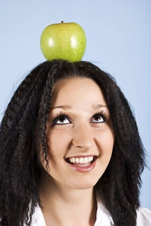 Youth female standing with an green apple on her head in profile,smiling and looking up  on blue background photo