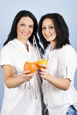 Young beautiful two women friends smile standing together and holding fresh orange and mandarin cut  in her hands,concept of healthy life photo