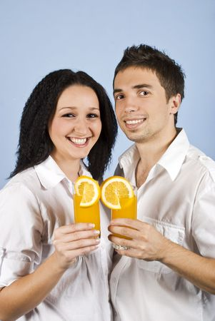 Youth couple smiling and laughing and holding glasses with fresh orange juice in their hands photo