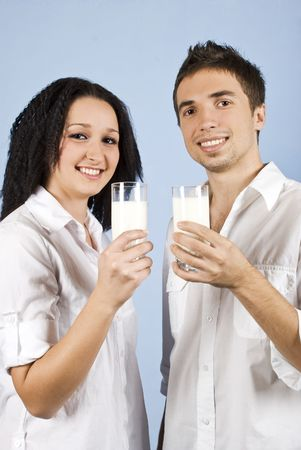 Happy youth couple standing together in front of image and holding glasses with milk on blue background photo