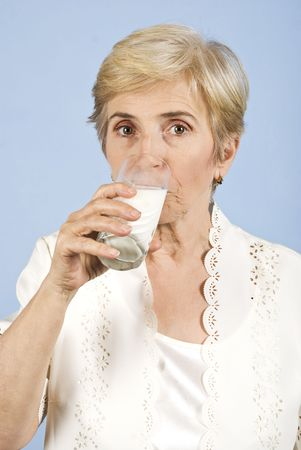 Older woman standing in front of image,looking you and drinking a glass with milk photo