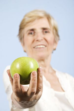 Senior woman giving you an green apple and smiling,focus on apple on blue background Stock Photo - 5591548