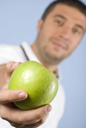 Man holding an green apple in his hand on blue background,focus on apple Stock Photo - 5591561