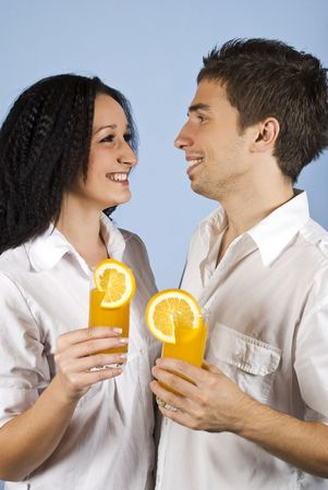 Happy young couple standing face to face and holding glasses with fresh orange juice and laughing together on blue background photo