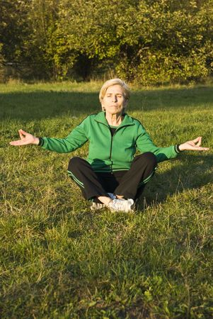Senior woman doing yoga lotus position outdoors in the park photo