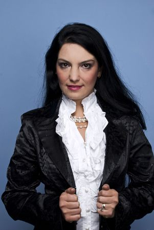 Modern brunette woman wearing an elegant outfit with a black shinny satin jacket ,white shirt and pearls on blue background Stock Photo - 5786904