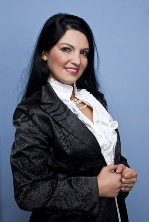 Beautiful smiling elegant woman standing in profile  and looking at you,she wearing a shinny black satin jacket and a modern white shirt accessories pearls for a special occassion on blue background Stock Photo - 5786906