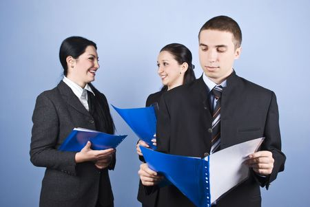 Business man being serious standing in front of camera reading a contract and his colleagues women holding contracts or paperwork and laughing together on blue background photo