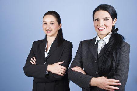mains crois�es: Deux belles jeunes femmes d'affaires permanent avec les mains crois�es et souriant pour vous sur fond bleu Banque d'images