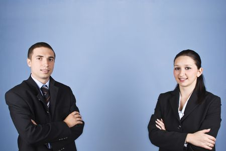 Two business people ,young man and woman standing with arms folded and smiling for you on blue background,copy space in center for text message photo