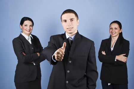 Three business people team with two women with arms folded and a business man in front of image giving thumbs up,concept of successful teamwork on blue background photo