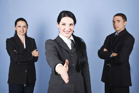 Three business people team standing and smiling for you with a businesswoman in front of image giving hand shake   photo