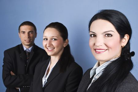 Cheerful group of three business people standing in semi profile and looking at you showing satisfaction and happiness photo