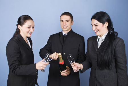 Happy business people team celebrating with champagne and having fun together on blue background photo