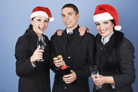 Business people celebrate Christmas with champagne and wearing Santa hats and laughing together on blue background photo