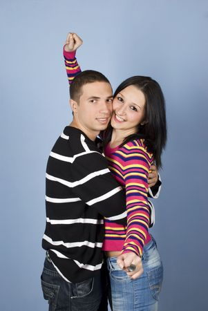 Happy young couple smiling and standing in a hug,they wearing warm clothes and jeans photo