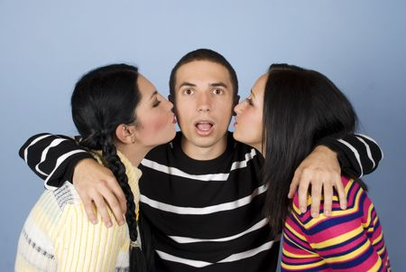 Young man looking surprised when two women kissing his cheeks,they wearing colorful sweaters on blue background photo