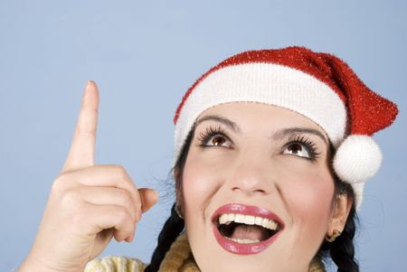 Head shot of happy surprised young Christmas woman pointing  and looking up to  to copy space on blue background Stock Photo - 5802101