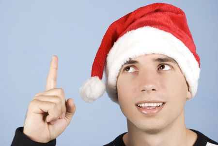 Young man wearing santa hat ,pointing and looking up to copy space on blue background photo