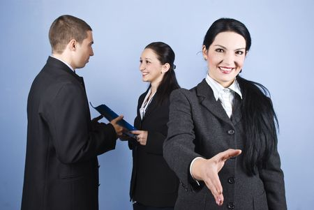 Welcome or joined in business with a business woman who standing with hand open and others persons standing in background give each other a folder with contract photo