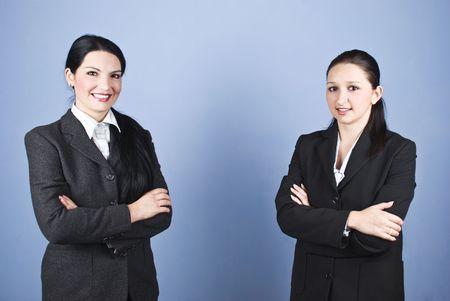 business for the middle: Two business women standing with arms folded and smiling,copy space for text message in the middle of image