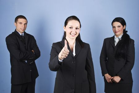 Business team successful with a business woman in front of image giving thumbs up and smiling for yo photo
