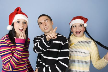 Group of young people friends wearing Santa hats and showing happiness and surprised faces while the man pointing somewhere up and they all looking there  photo