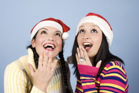 Beauty young two women showing surprised and happy faces while looking up at copy space ,they wearing Santa hat and exclaim :Wow! and holding their hands to mouths photo