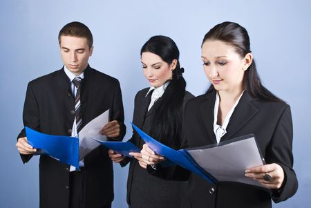 Business team people holding blue folders with contracts and reading in front of blue background Stock Photo - 5858727