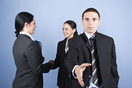 poign�es de main: Business handshakes with a businessman giving hand and other two woman shaking hands in background