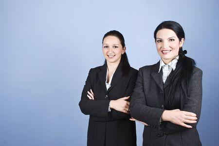 mani incrociate: Due donne d'affari in piedi uno vicino all'altro con le mani incrociate e sorriso per te, copia spazio per il messaggio di testo nella parte sinistra dell'immagine Archivio Fotografico