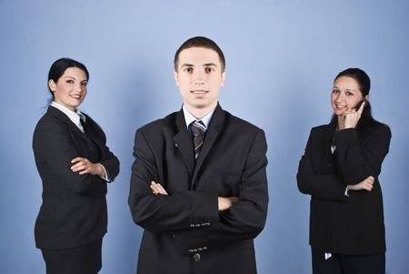 mani incrociate: Leader uomo di affari a fronte di immagine e dei suoi colleghi in background, una donna d'affari di parlare per telefono cellulare e l'altro in piedi con le mani incrociate e sorridente Archivio Fotografico