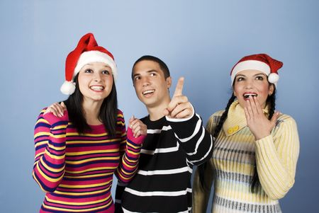 Christmas surprise with three friends,the man showing something and they all are surprised,happy and laughing together.(You can add in photo gifts,presents,promotions or snowflakes) photo