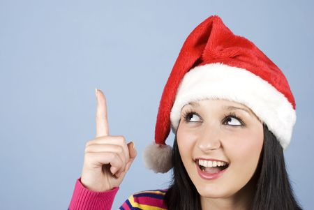 Girl with Santa hat pointing up to copy space and  looking very surprised and happy photo