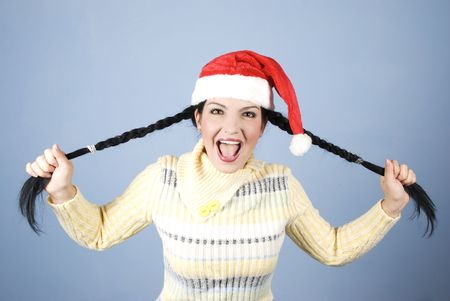 Funny Christmas girl   with Santa hat her pulling  pigtails screaming and laughing in front of blue background