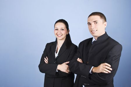 mains crois�es: Portrait of two business young people standing with hands crossed and smiling over blue background,copy space for text message in left part of image