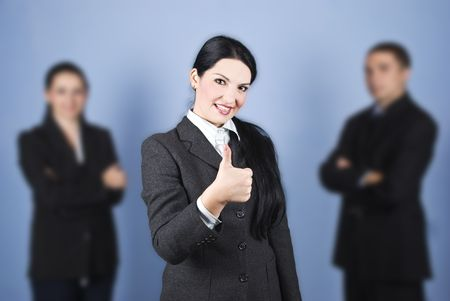Business woman leader giving thumbs up in the middle of her colleagues and smiling,concept of successful teamwork Stock Photo - 5878565