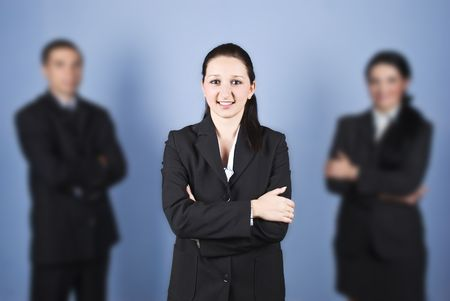 Young business woman leader standing with hands crossed and smiling for you in the middle of two colleagues partners Stock Photo - 5878560