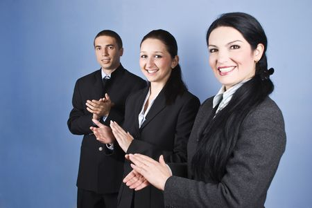 front facing: Congratulations!Successful business team people clapping and smiling over blue background Stock Photo