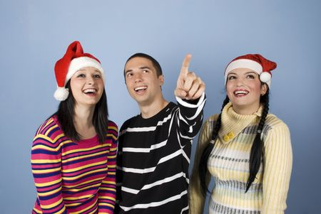 Happy young  Christmas  friends people with Santa hats  laughing together while the man pointing up somewhere towards the top right photo