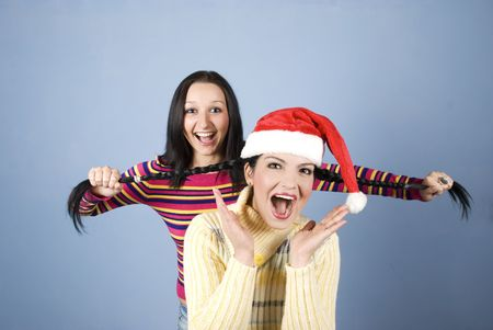 A funny  girl with Santa hat having her pigtails pulled by her friend and both laughing and shouting and have fun photo