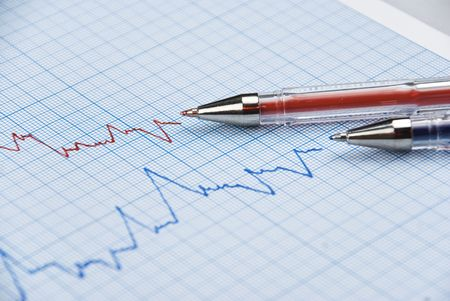 Financial chart shows  a graph in two colors red and blue with two pens made on millimeter paper,selective focus Stock Photo - 5938290