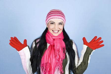 Excited young woman in winter clothes smiling and standing with open hands over blue background photo