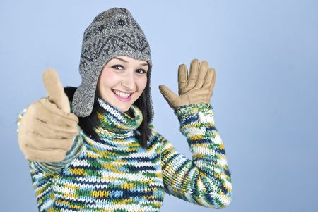 Happy winter girl  in hat and gloves giving thumbs up over blue background,copy space for text message in right part of image Stock Photo - 5980541