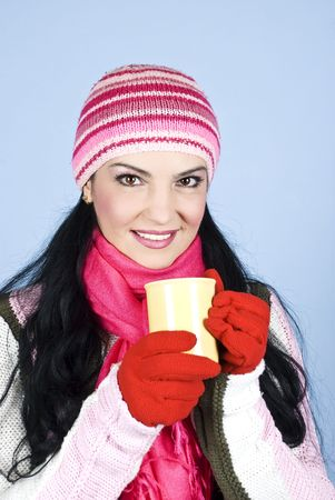 Happy winter woman wearing cap,scarf and gloves and holding a cup of hot tea in her hands and smiling for you over blue background photo